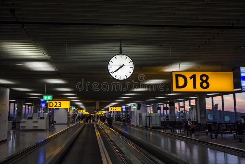 Κυλιόμενη σκάλα που περνά από τις πύλες της αίθουσας Δ του αερολιμένα Schiphol με τις πύλες στις πλευρές με τους επιβάτες έτοιμου στοκ φωτογραφίες