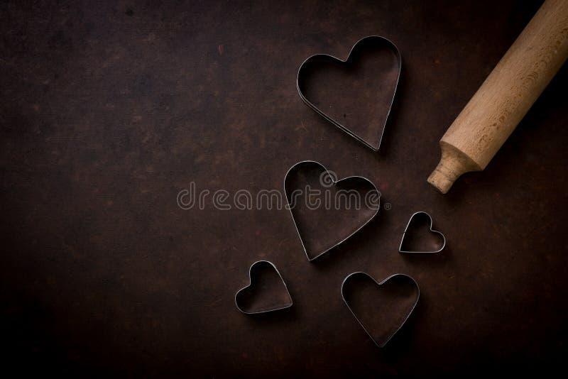 Κυλώντας καρφίτσα με τους κόπτες μπισκότων με μορφή μιας καρδιάς στοκ εικόνες