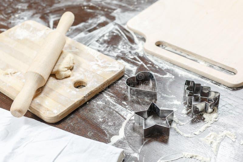 Κυλώντας καρφίτσα, ξύλινοι πίνακες με το αλεύρι, τη ζύμη και τους κόπτες μπισκότων με μορφή της καρδιάς ` στοκ εικόνες