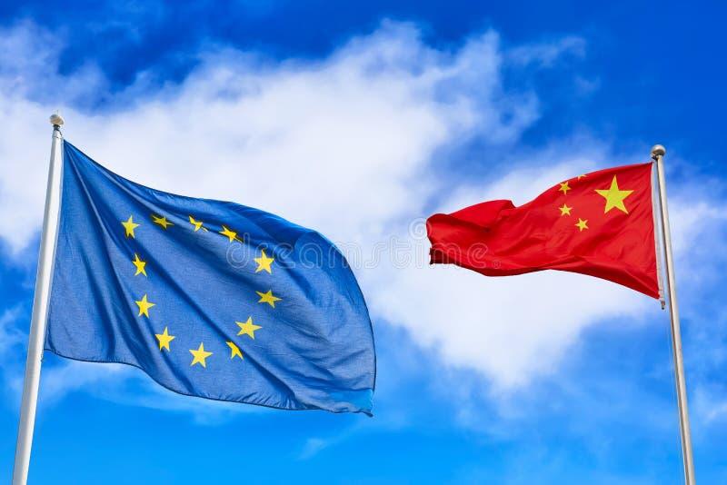 Κυματίζοντας εθνικές σημαίες της Ευρωπαϊκής Ένωσης της Κίνας και στο κλίμα μπλε ουρανού Έννοια συνεργασίας στοκ εικόνα με δικαίωμα ελεύθερης χρήσης