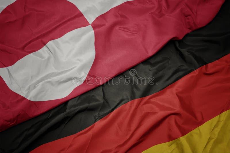 κυματίζοντας ζωηρόχρωμη σημαία της Γερμανίας και εθνική σημαία της Γροιλανδίας στοκ φωτογραφίες με δικαίωμα ελεύθερης χρήσης