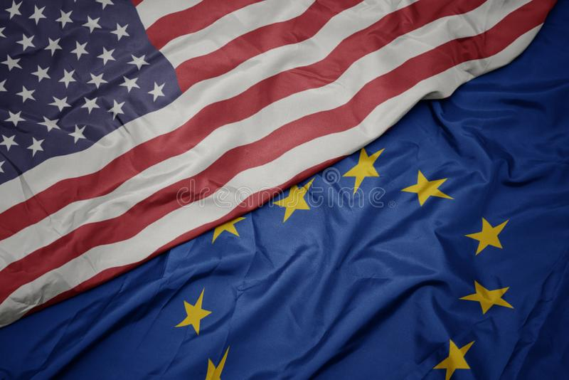 κυματίζοντας ζωηρόχρωμη σημαία της ευρωπαϊκής ένωσης και σημαία των Ηνωμένων Πολιτειών της Αμερικής στοκ εικόνα