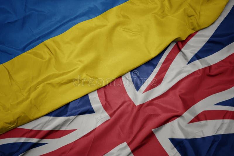 κυματίζοντας ζωηρόχρωμη σημαία της Μεγάλης Βρετανίας και εθνική σημαία της Ουκρανίας στοκ φωτογραφία με δικαίωμα ελεύθερης χρήσης