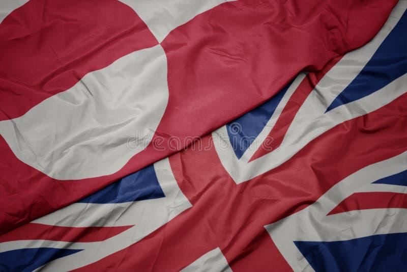 κυματίζοντας ζωηρόχρωμη σημαία της Μεγάλης Βρετανίας και εθνική σημαία της Γροιλανδίας στοκ φωτογραφίες με δικαίωμα ελεύθερης χρήσης