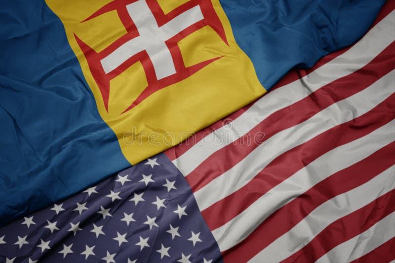κυματίζοντας ζωηρόχρωμη σημαία των Ηνωμένων Πολιτειών της Αμερικής και εθνική σημαία της Μαδέρας r στοκ εικόνες