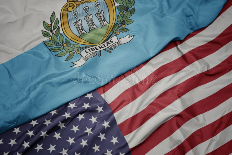 κυματίζοντας ζωηρόχρωμη σημαία των Ηνωμένων Πολιτειών της Αμερικής και εθνική σημαία του Άγιου Μαρίνου r στοκ φωτογραφία με δικαίωμα ελεύθερης χρήσης