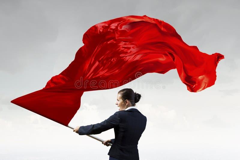 Κυματίζοντας κόκκινη σημαία γυναικών Μικτά μέσα στοκ εικόνες