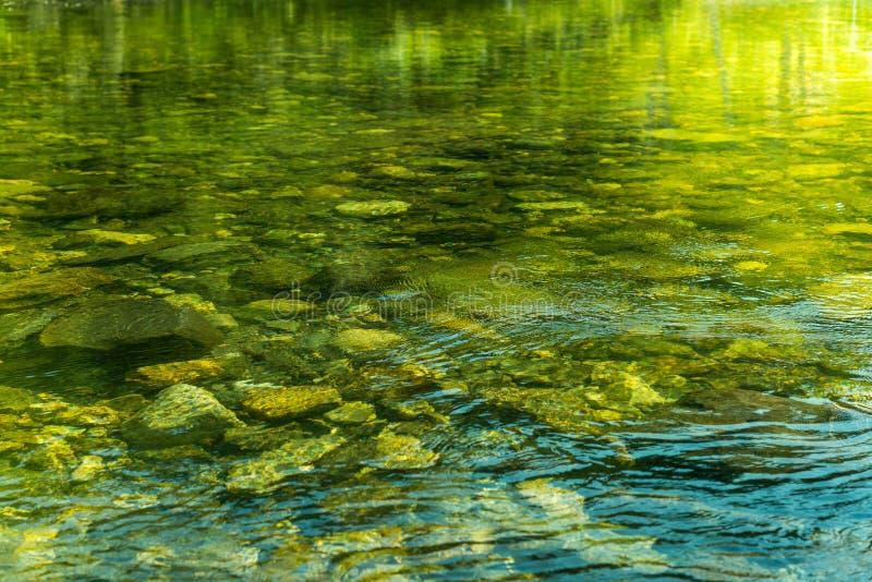 Κυματίζοντας νερό με την ηλιαχτίδα και πέτρες στο νερό στοκ φωτογραφίες