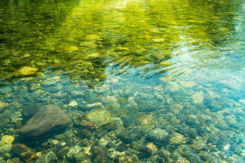 Κυματίζοντας νερό με την ηλιαχτίδα και πέτρες στο νερό στοκ εικόνες