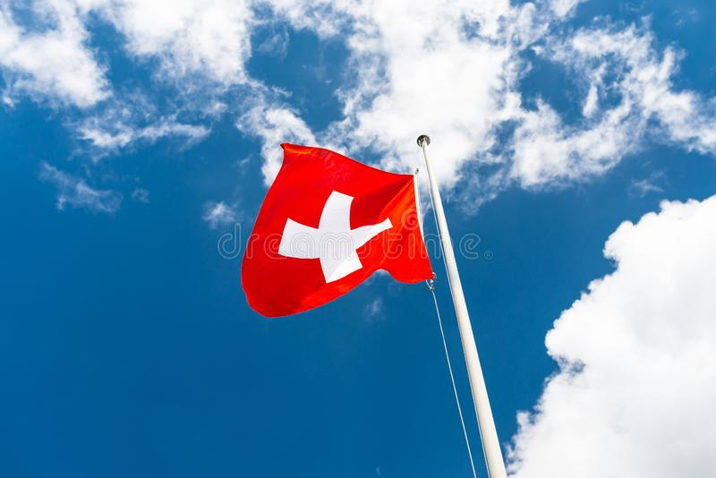Κυματίζοντας στον αέρα στο αριστερό, η σημαία της ένωσης της Ελβετίας στον ιστό, στα πλαίσια του μπλε ουρανού με τα άσπρα σύννεφα στοκ εικόνα με δικαίωμα ελεύθερης χρήσης