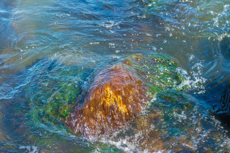 Κυματισμοί γύρω από μια mossy πέτρα σε μια λίμνη στοκ εικόνα