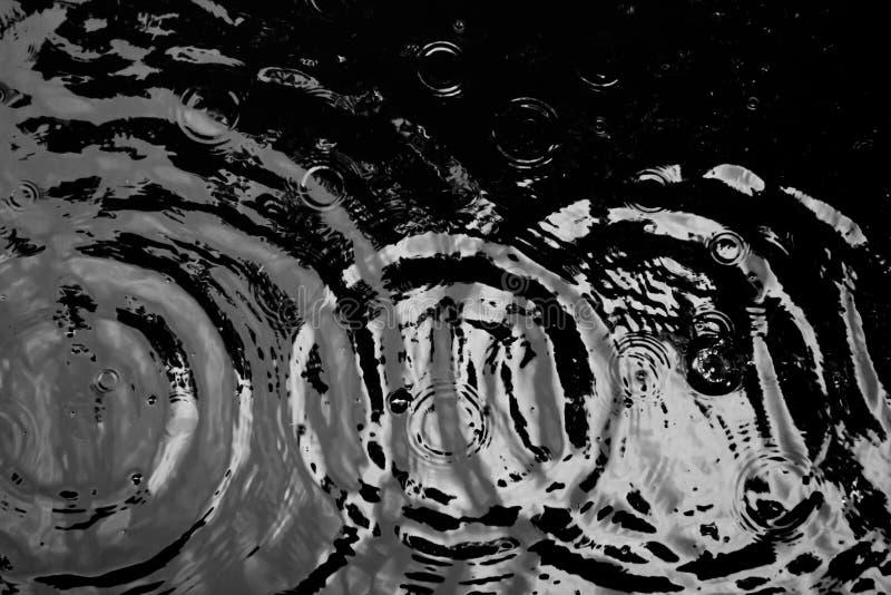 Κυματισμοί νερού από μια πτώση του νερού στο σκοτάδι στοκ φωτογραφία