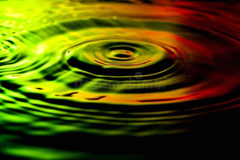 Κυματισμοί νερού στο συμπαθητικό κιτρινοπράσινο κόκκινο υπόβαθρο στοκ εικόνες