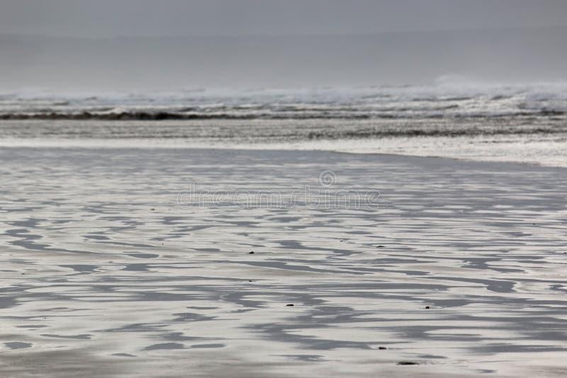 Κυματισμοί στην άμμο σε μια παραλία στοκ φωτογραφία