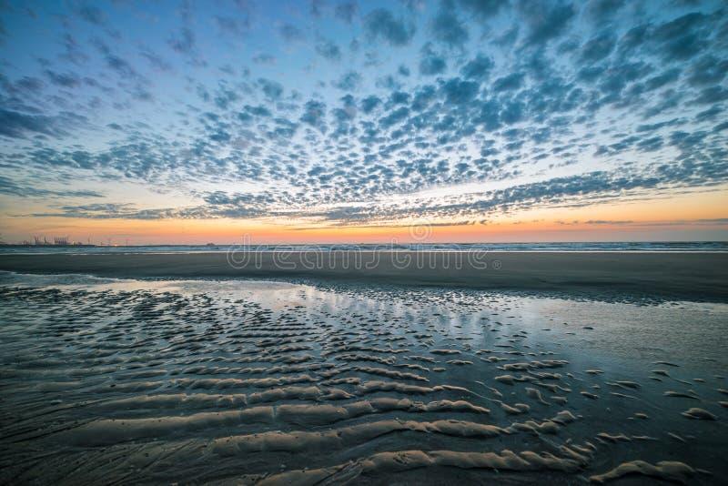 Κυματισμοί στην άμμο της παραλίας με έναν όμορφο ουρανό βραδιού στοκ εικόνα