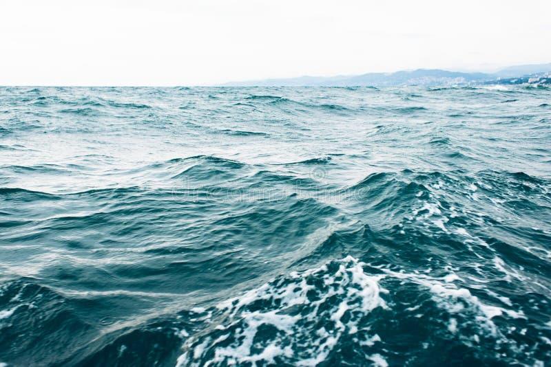 Κυματισμοί στο μπλε θαλάσσιο νερό με τον άσπρο αφρό, φυσικό υπόβαθρο θάλασσας στοκ εικόνα