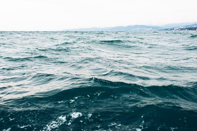 Κυματισμοί στο μπλε θαλάσσιο νερό με τον άσπρο αφρό, φυσικό υπόβαθρο θάλασσας στοκ εικόνες με δικαίωμα ελεύθερης χρήσης