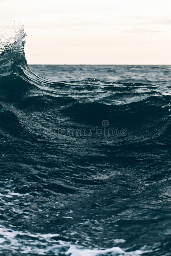 Κυματισμοί στο μπλε θαλάσσιο νερό με τον άσπρο αφρό, φυσικό υπόβαθρο θάλασσας στοκ εικόνα με δικαίωμα ελεύθερης χρήσης