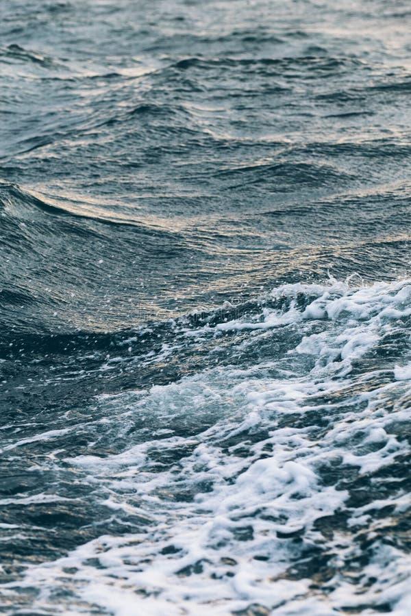 Κυματισμοί στο μπλε θαλάσσιο νερό με τον άσπρο αφρό, φυσικό υπόβαθρο θάλασσας στοκ φωτογραφία
