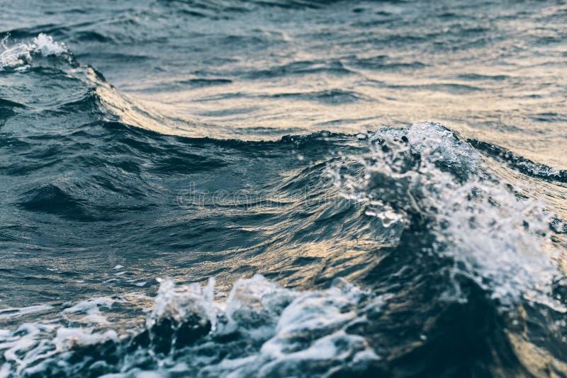 Κυματισμοί στο μπλε θαλάσσιο νερό με τον άσπρο αφρό, φυσικό υπόβαθρο θάλασσας στοκ εικόνες