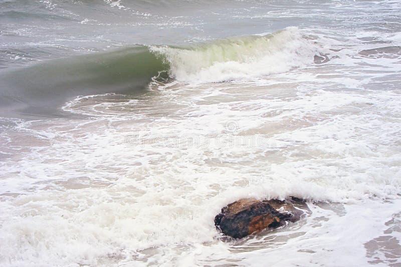 Κυματωγή κυμάτων θάλασσας και άγρια πέτρα στην αμμώδη παραλία στο στροβιλιμένος νερό στοκ φωτογραφία με δικαίωμα ελεύθερης χρήσης
