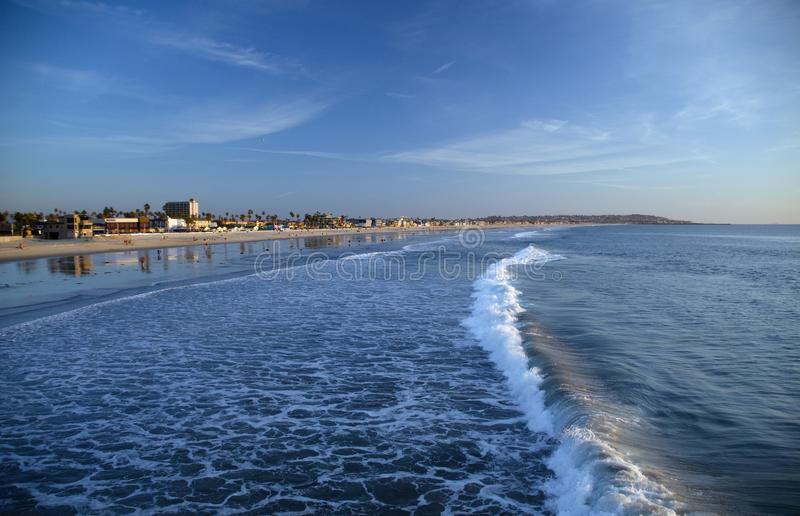 Κυματωγή προσοχής στην ειρηνική παραλία που τονίζεται από το πρόωρο ηλιοβασίλεμα από μια αποβάθρα στοκ φωτογραφίες με δικαίωμα ελεύθερης χρήσης