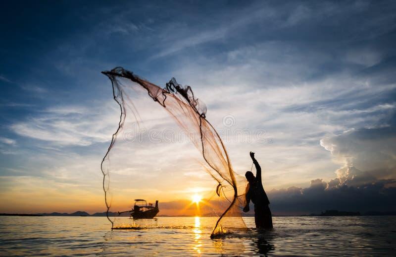 Κυνήγι για το ηλιοβασίλεμα Σκιαγραφία του μη αναγνωρισμένου πετώντας διχτυού του ψαρέματος ψαράδων στοκ εικόνες