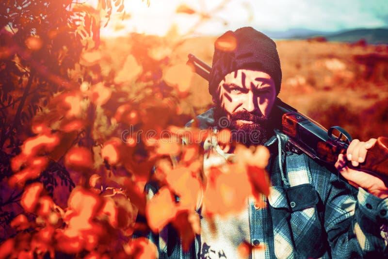 Κυνηγός Περίοδος κυνηγιού, εποχή φθινοπώρου Κυνηγός με ένα πυροβόλο όπλο κυνηγιού και μια μορφή κυνηγιού για να κυνηγήσει στο δασ στοκ εικόνα με δικαίωμα ελεύθερης χρήσης