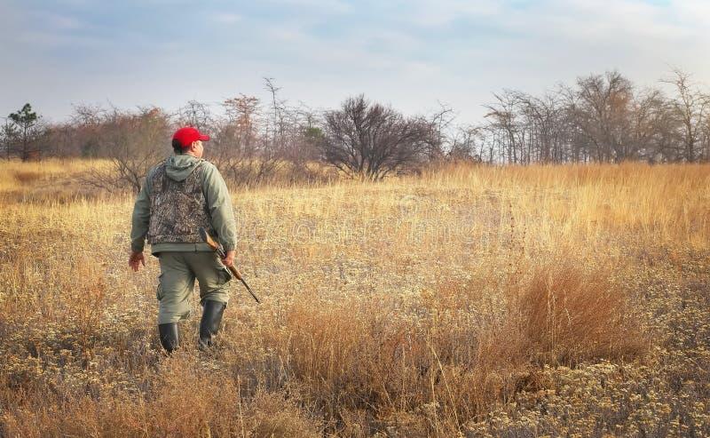 Κυνηγός που κινείται με το κυνηγετικό όπλο που ψάχνει το θήραμα στοκ εικόνες