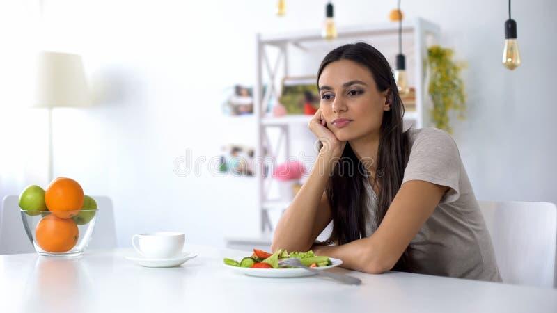 Κυρία δυσαρεστημένη με τη σαλάτα, που ονειρεύεται για το άχρηστο φαγητό, υγιεινή λίγων θερμίδων διατροφή στοκ εικόνα