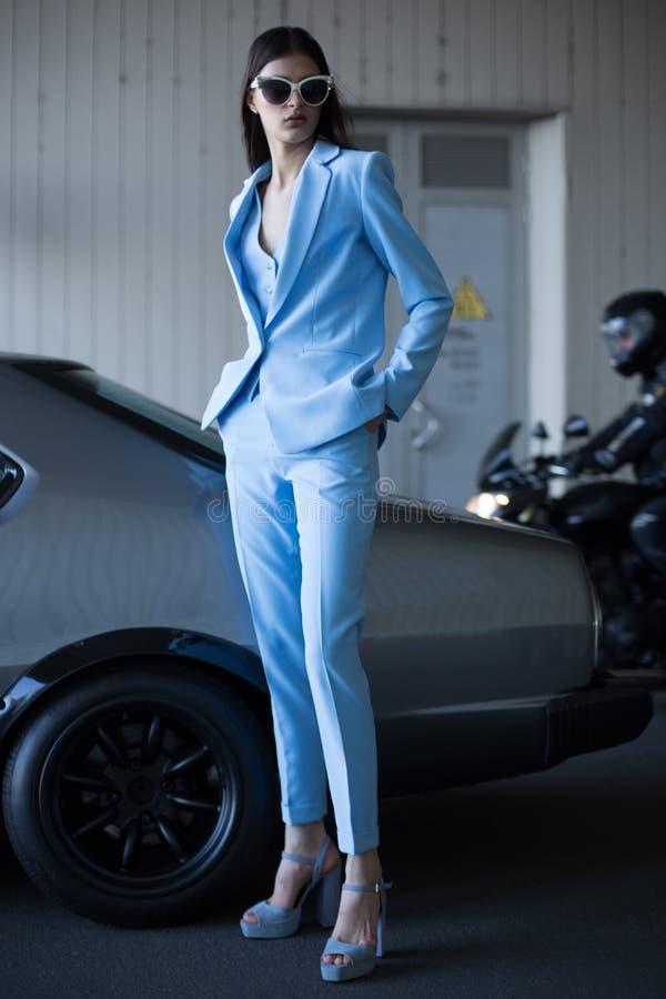 Κυρία μαφίας έξω από το japonese αυτοκίνητο στο θαλάσσιο λιμένα Κορίτσι μόδας που στέκεται δίπλα σε ένα αναδρομικό σπορ αυτοκίνητ στοκ εικόνες με δικαίωμα ελεύθερης χρήσης