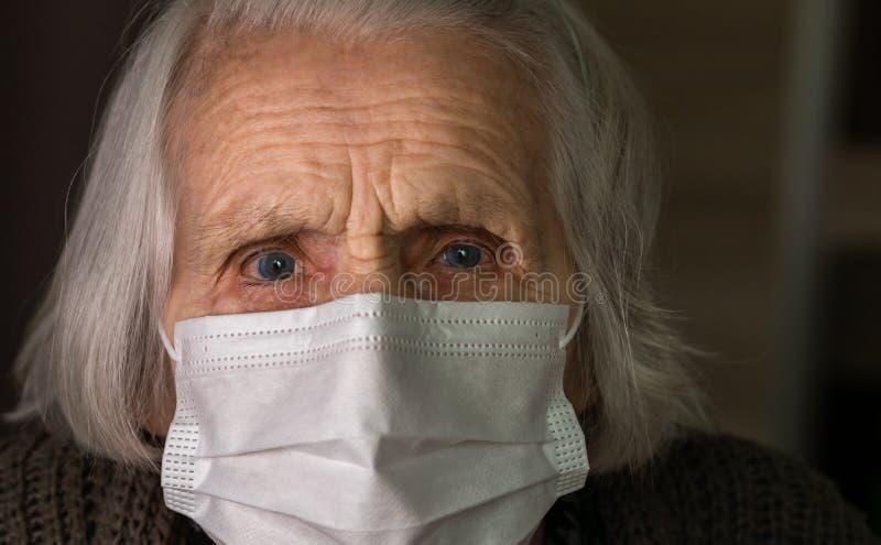 Κυρία με μάσκα υγιεινής προσώπου Γριά γυναίκα με φοβισμένα μάτια Έννοια COVID-19, κοινωνική απόσταση στοκ εικόνες