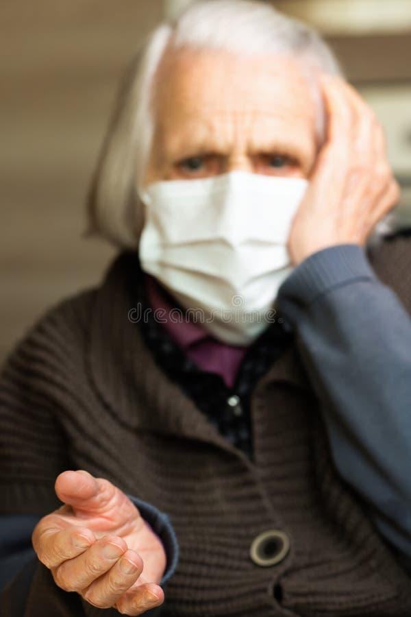 Κυρία με μάσκα υγιεινής προσώπου σε εστίαση Γριά γυναίκα με φοβισμένα μάτια Έννοια COVID-19, κοινωνική απόσταση στοκ εικόνες