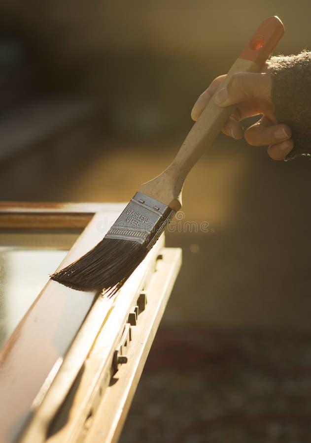 Κυρία που ανανεώνει το παλαιό ξύλινο παράθυρο στοκ εικόνα