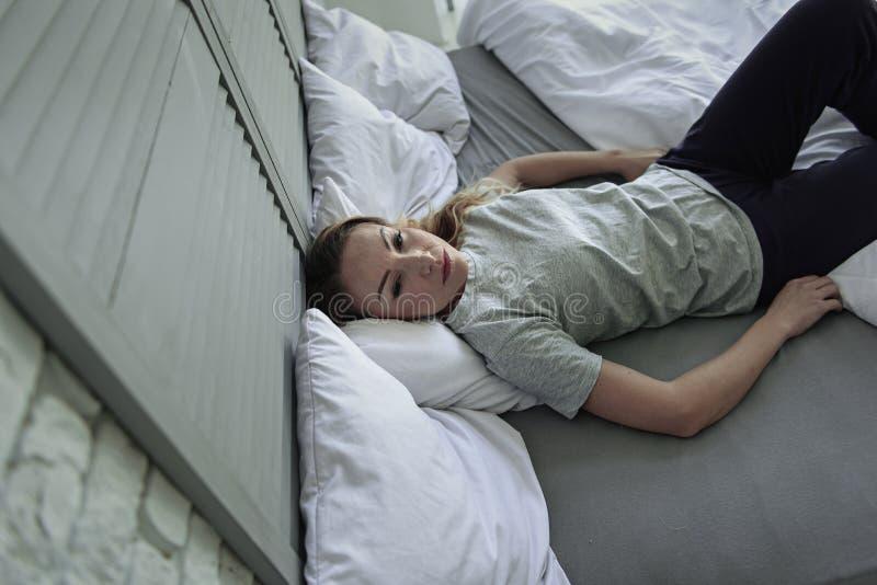 Κυρία που βρίσκεται στο πλαίσιο κρεβατιού στοκ φωτογραφίες