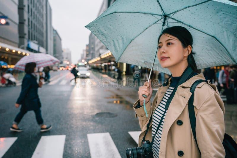 Κυρία που διασχίζει το δρόμο με μια μπλε ομπρέλα στοκ εικόνες