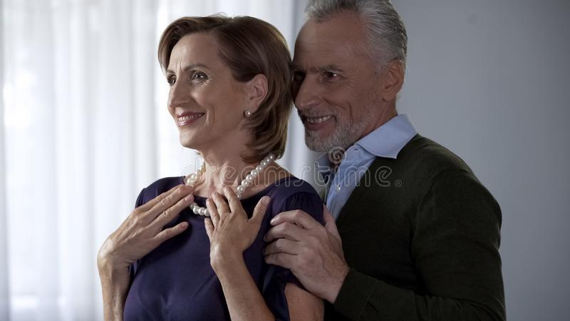 Κυρία που θαυμάζει το πολύτιμο δώρο από την αγάπη του συζύγου, ευτυχές ανώτερο χαμόγελο ζευγών στοκ φωτογραφία με δικαίωμα ελεύθερης χρήσης
