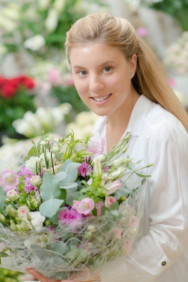 Κυρία που κρατά τα μεγάλα λουλούδια ανθοδεσμών στοκ εικόνες