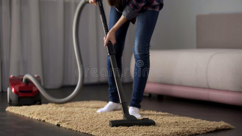 Κυρία που σκουπίζει προσεκτικά το χαλί κρεβατιών με ηλεκτρική σκούπα, που φέρνει το σπίτι για να διατάξει, πρόληψη αλλεργίας στοκ φωτογραφία με δικαίωμα ελεύθερης χρήσης