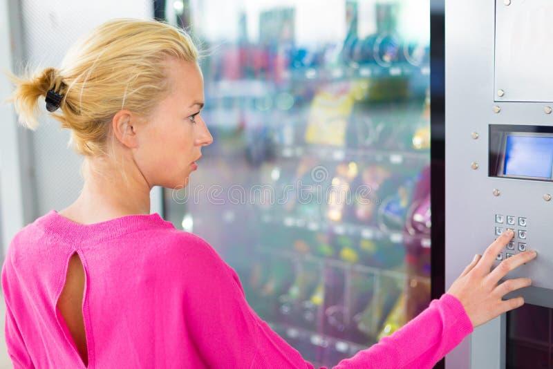 Κυρία που χρησιμοποιεί μια σύγχρονη μηχανή πώλησης στοκ φωτογραφία