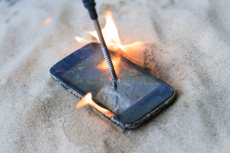 κυψελοειδές τηλέφωνο στην άμμο παραλιών έχει ένα καρφί μετάλλων σε το καίει με ανοίγει πυρ στοκ εικόνα