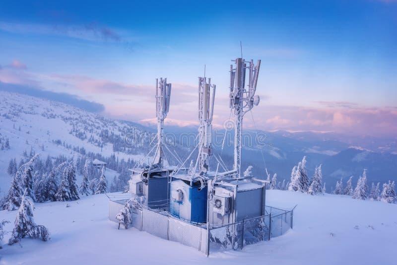 Κυψελοειδής σταθμός βάσης στο χιονώδη λόφο χειμερινών βουνών στο φως ηλιοβασιλέματος στοκ φωτογραφία με δικαίωμα ελεύθερης χρήσης