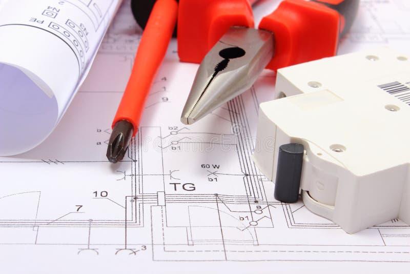 Κυλημένα ηλεκτρικά διαγράμματα, ηλεκτρικά θρυαλλίδα και εργαλεία εργασίας στο κατασκευαστικό σχέδιο του σπιτιού στοκ εικόνα με δικαίωμα ελεύθερης χρήσης