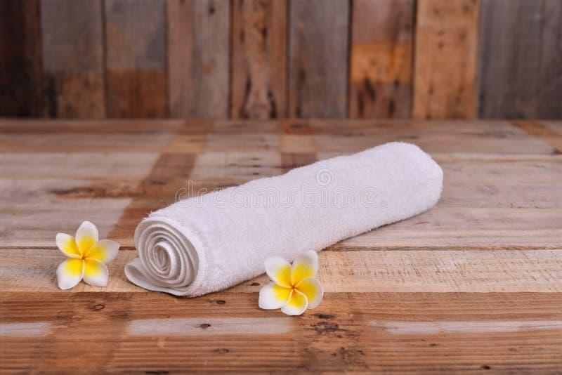 Κυλημένη επάνω άσπρη πετσέτα με τα λουλούδια Frangipani στοκ φωτογραφία με δικαίωμα ελεύθερης χρήσης