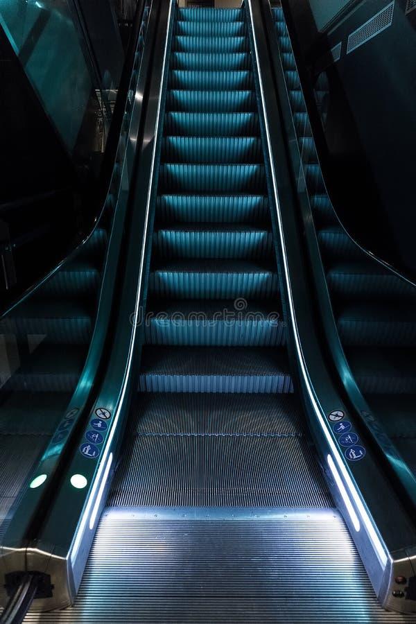 Κυλιόμενες σκάλες με το μπλε φως στοκ εικόνα