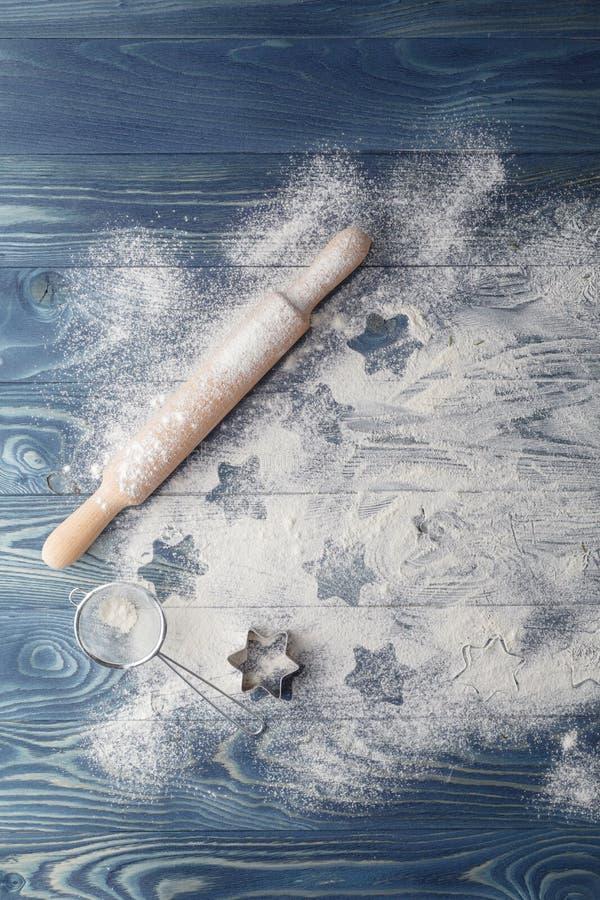 Κυλώντας καρφίτσα, αλεύρι και μορφές για τα μπισκότα στους πίνακες στοκ εικόνα