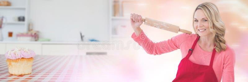 Κυλώντας καρφίτσα εκμετάλλευσης αρχιμαγείρων εγχώριου ψησίματος με τη μετάβαση cupcake στοκ φωτογραφίες