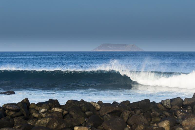 Κυλώντας κύματα, νησί και βράχοι στοκ εικόνα