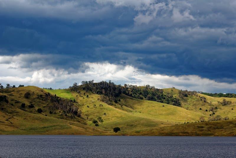 Κυλώντας λόφοι στη λίμνη Lyell από τον καλυμμένο ουρανό στοκ εικόνα