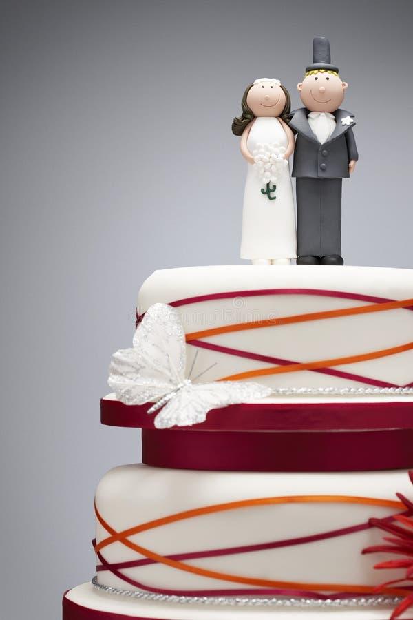 Κωμικά ειδώλια νυφών και νεόνυμφων πάνω από το γαμήλιο κέικ στοκ φωτογραφίες